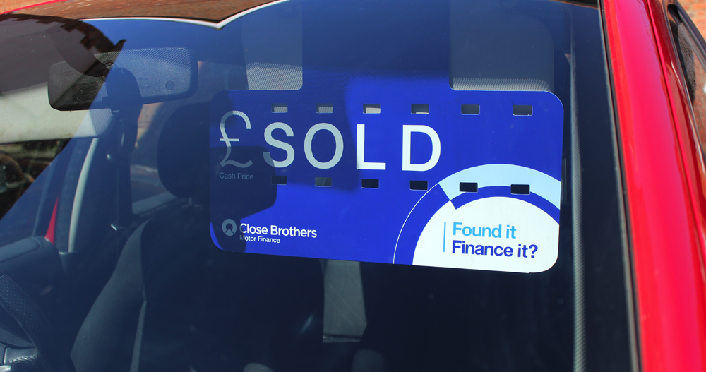 Close Brothers Motor Finance sold sign in red car