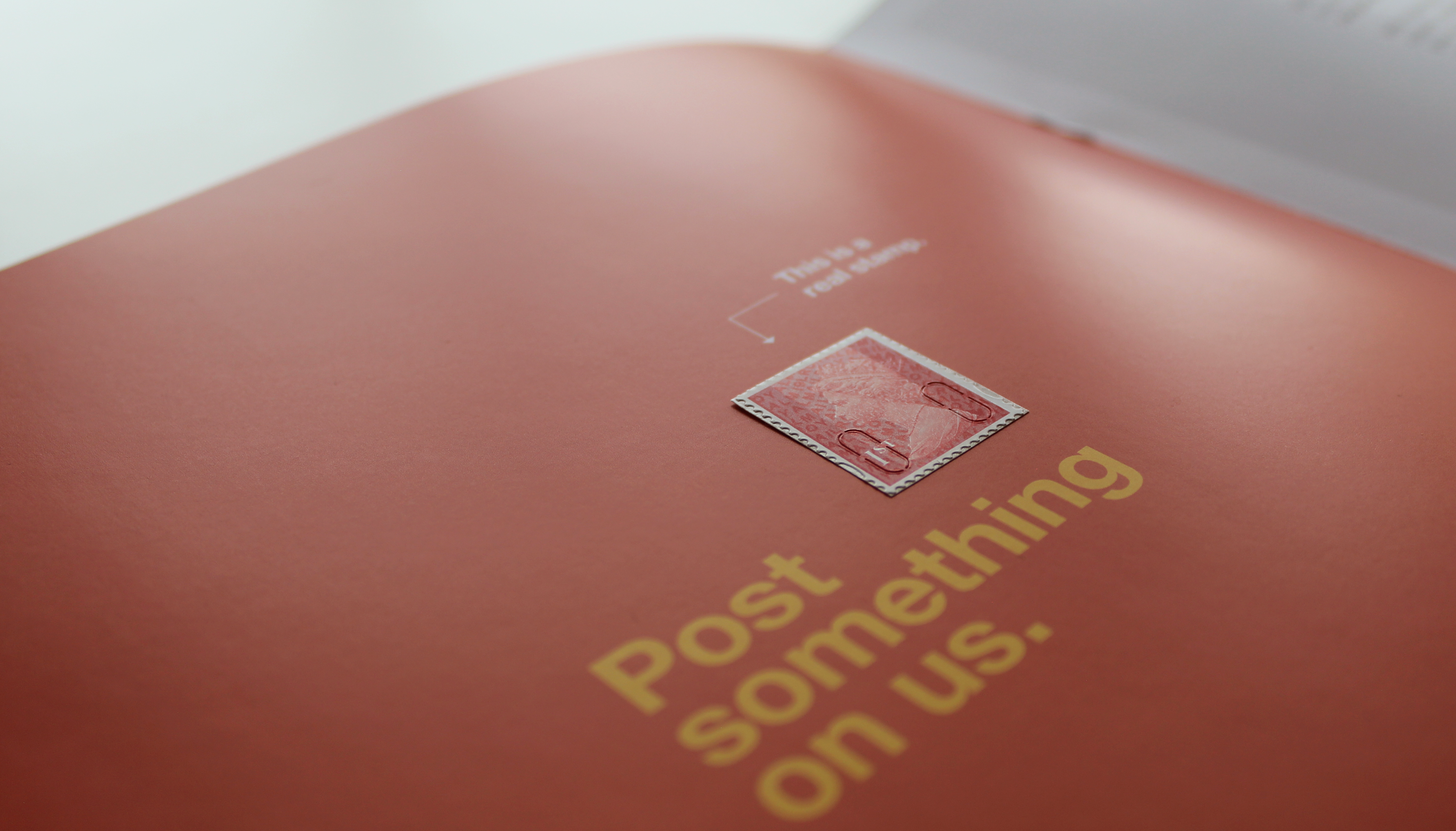 Printed brochure with 1st Class postage stamp saying mail something on us