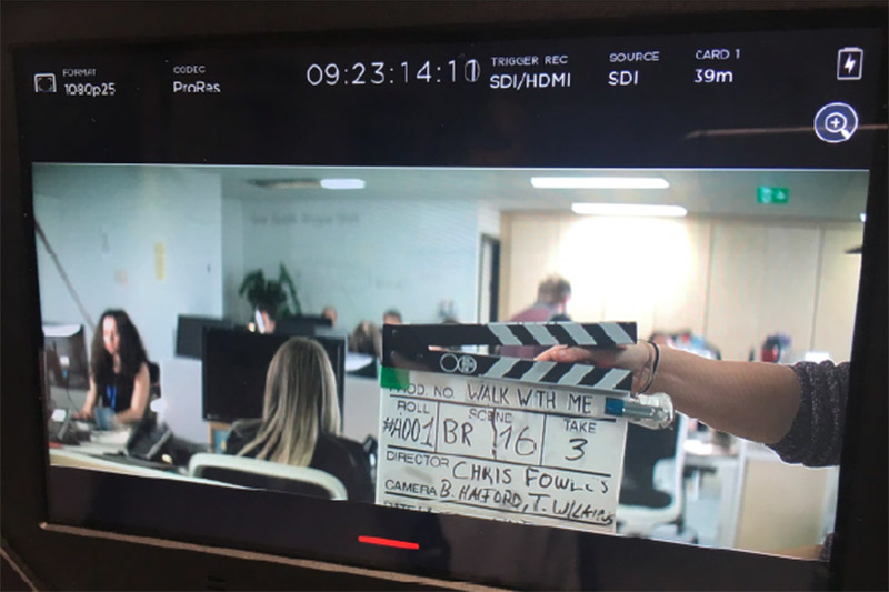 Clapperboard on screen during filming of video